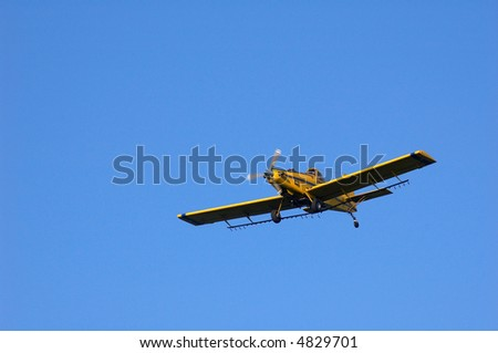 A crop dusting plane in flight. - stock photo
