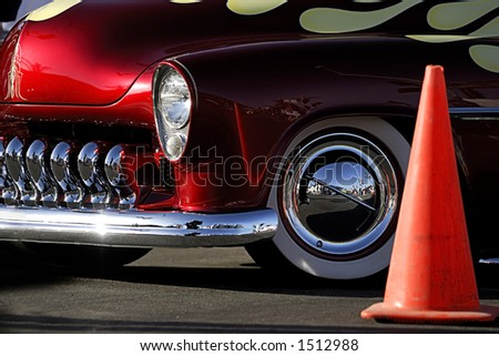 A cropped image of a fully restored classic old car with lots of shiny chrome.This image includes a bright orange traffic cone. - stock photo