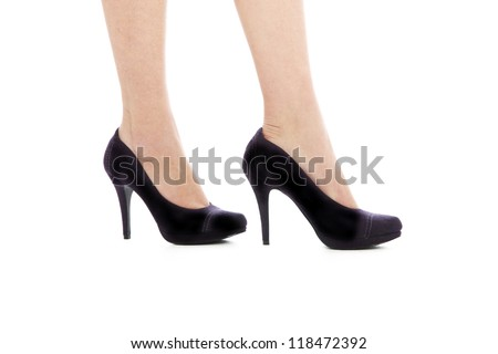 A cropped shot of a woman's lower legs in elegant black high-heeled court shoes