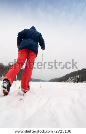 A cross country skier out on a refreshing trip over a frozen lake. - stock photo