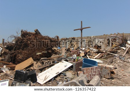 A cross held together by a tattered United States flag is raised above a home totally destroyed by a devastating tornado as proof of the homeowners determination to overcome natures wrath. - stock photo