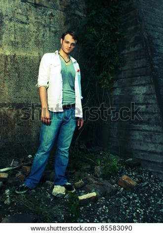 A cross processed photo of a man by an old wall - stock photo