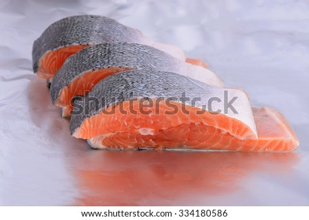A cross section of a salmon on a foil - stock photo