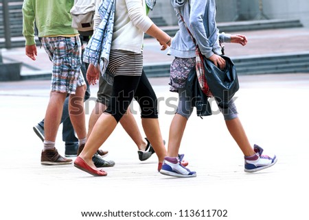 A crowd moving against a background of an urban landscape. Young people. - stock photo