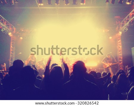 a crowd of people at a concert clapping their hands with a slight blur toned with a retro vintage instagram filter effect app or action - stock photo