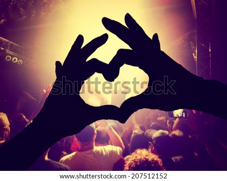 a crowd of people at a concert  with a heart silhouette on the singer toned with a vintage retro instagram filter - stock photo