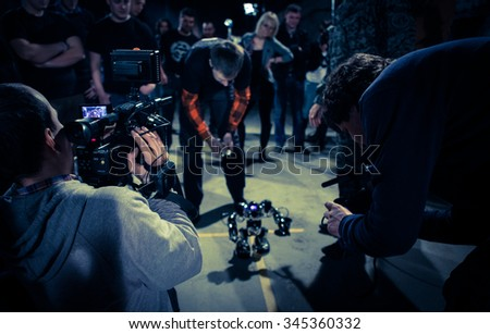 A crowd of people shooting a video with a robot - stock photo