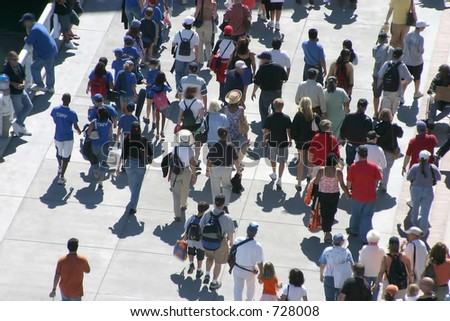 A crowd of people stroll on a sidewalk. All exposed faces are motion blurred. - stock photo