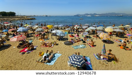 A crowd of vacationers enjoy the warm beaches of Cannes, France during the summer - stock photo