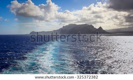 A cruise ship leaves a wake as it departs the Hawaiian island of Kauai - stock photo