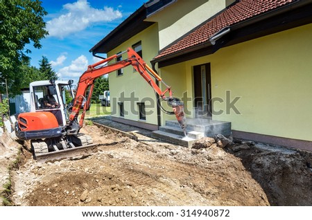 A crusher is demolishing a house. Rebuilding a family house with a crusher that is destroying the concrete stairs. - stock photo