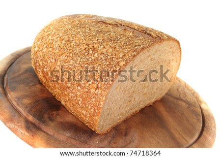 a crusty loaf of bread on a wooden board on white background
