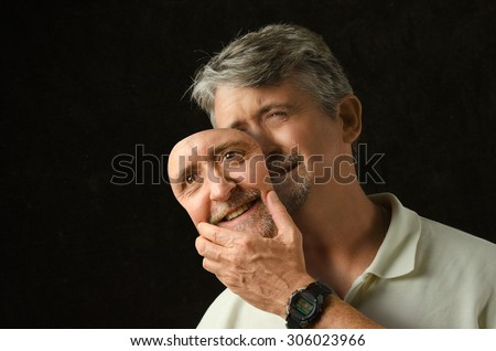 A crying depressed bipolar disorder man is trying to hide his tears with a fake smile happiness mask that looks exactly like his face. - stock photo