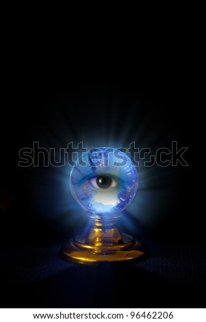 A crystal ball on black with a blueish glow and an eye peering out at you. - stock photo