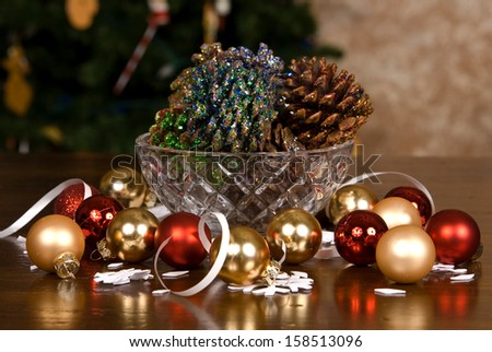 A crystal bowl of colorful pine cones and bulbs sitting on a wooden table top in front of a Christmas tree. - stock photo