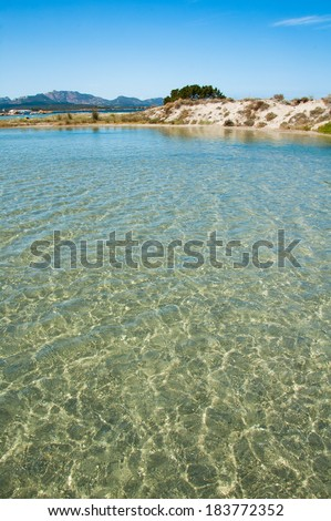A crystal-clear water in foreground with a sand dune on the background, San Teodoro, Sardinia, Italy - stock photo