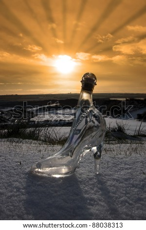 a crystal glass slipper in a snow covered irish golf course at sunset for a concept on ladies golf - stock photo