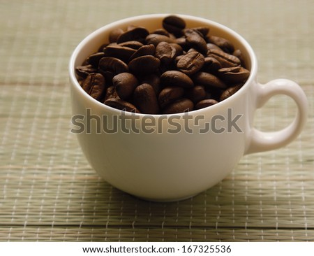 A cup and coffee beans, from above - stock photo