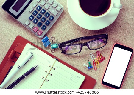 A cup coffee smart phone and office supplies on the table - stock photo