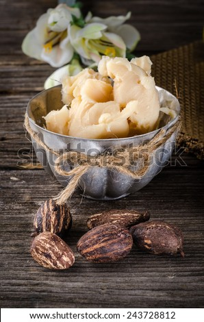 A cup full with shea butter with shea nuts on a rusty table - stock photo