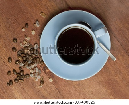 A cup of black coffee in a blue cup, with coffee grains and cane sugar, on a dark wooden texture, shot from above, with copyspace