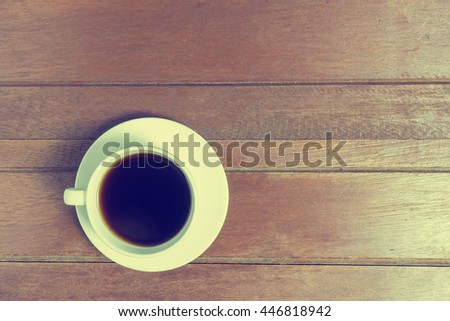 A cup of black coffee put on old oak wood wooden table texture abstract background. Top view with vintage tone and Copy space