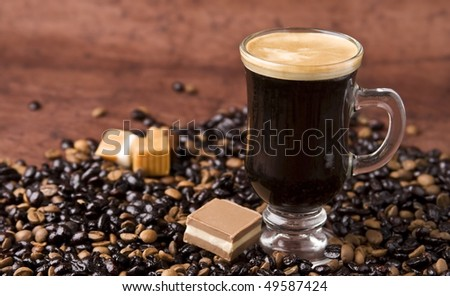 A cup of black coffee with chocolate and coffee beans. - stock photo