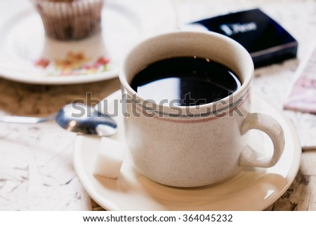 A cup of black coffee with sugar and sweet cupcake - stock photo