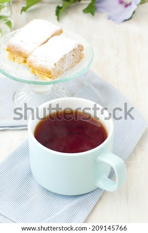 a cup of black tea and cakes