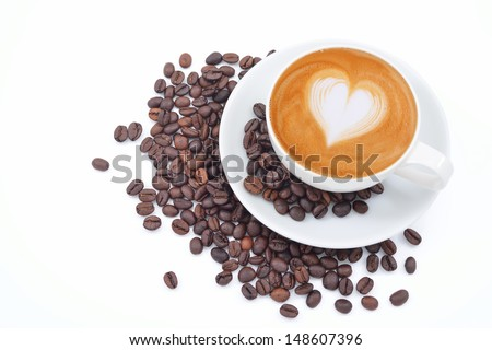 A cup of cafe latte and coffee beans on white - stock photo