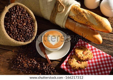A cup of cafe latte with coffee beans and bread - stock photo