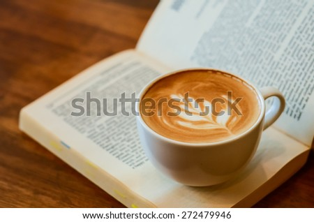A cup of caffe latte place on a book or a novel - stock photo
