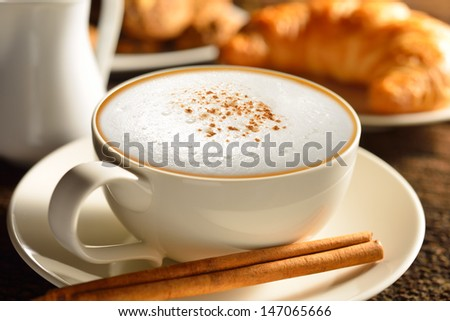 A cup of cappuccino and croissant - stock photo