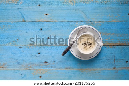 A cup of cappuccino on a blue wooden table, free copy space - stock photo