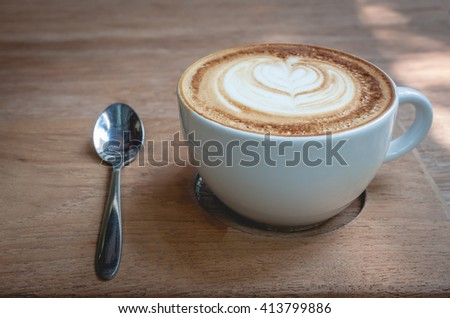 A cup of cappucino on a wood background - stock photo