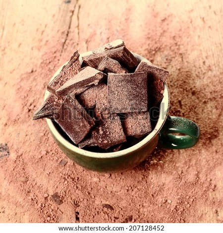 A cup of chocolate chips on a wooden table. - stock photo