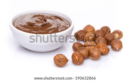 A cup of chocolate hazelnut spread with hazelnuts, isolated on white - stock photo