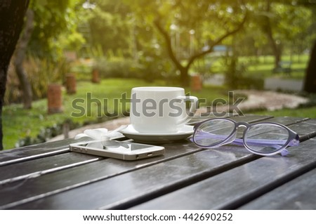 a cup of coffe on table in garden at sunny day, blurred