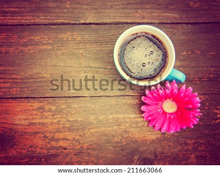 a cup of coffee and a flower on a wooden texture background toned with a retro vintage instagram filter  - stock photo