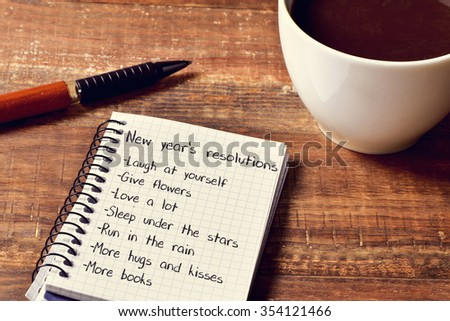 a cup of coffee and a notebook with a list of new years resolutions, such as laugh at yourself, give flowers, love a lot, sleep under the stars or run in the rain, on a rustic wooden table - stock photo