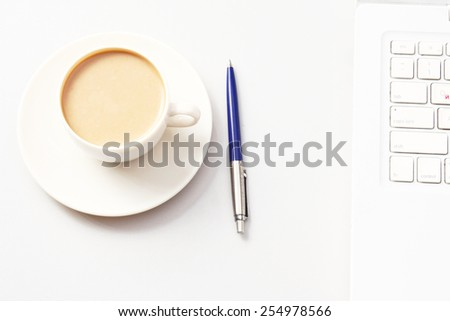 A cup of coffee and a pen near a laptop. Business concept. - stock photo