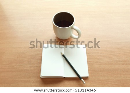 A cup of coffee and a pencil over blank notebook on a wooden desk from above