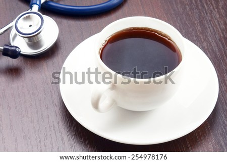A cup of coffee and a statoscope on a desk - stock photo
