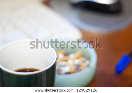 A cup of coffee and an ashtray on the office desk. Substances abuse. Morning habit. - stock photo