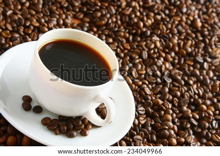 a cup of coffee and coffee beans - stock photo