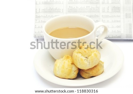 a cup of coffee and eclairs against newspaper - stock photo