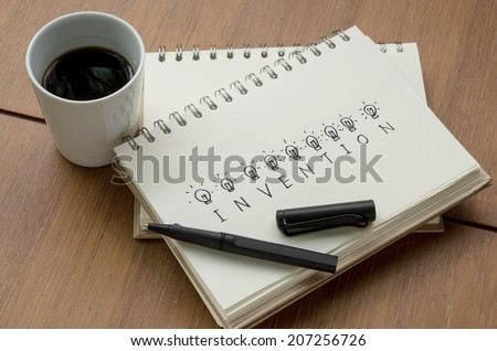A Cup of Coffee and Invention Concept Idea Sketch with Pen - stock photo