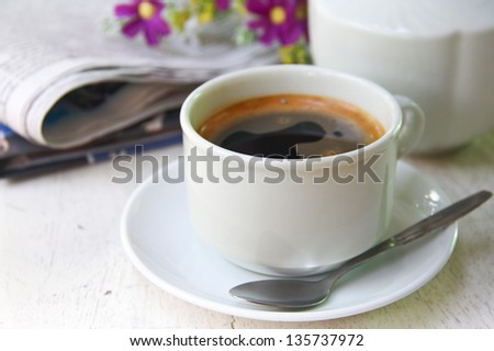 a cup of coffee and newspaper on table