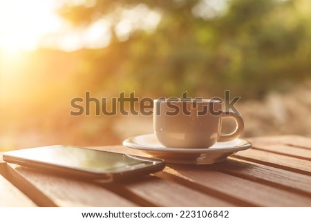 A cup of coffee and smartphone on the table