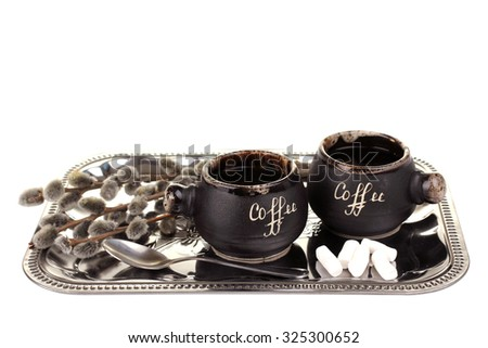 a Cup of coffee and spoon on the dressing on a white isolated background